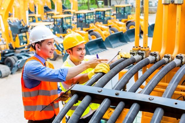 Mecánico de motores asiático discutiendo con la lista de tareas del ingeniero en el taller de máquinas de construcción