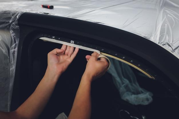 Mecánico preparando un coche para pintar protegiendo los bordes.