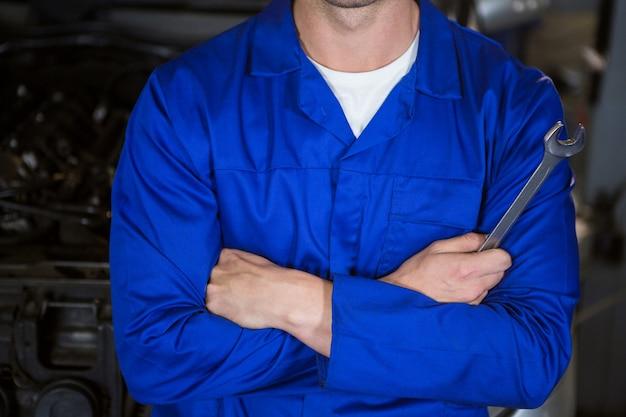 Mecánico que se coloca en el garaje de reparación