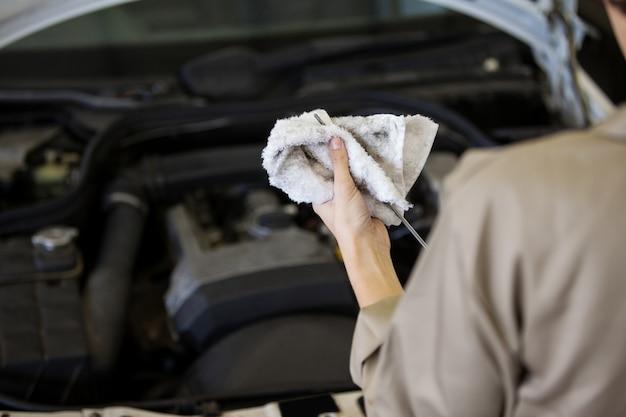 Mecánico que controla el nivel de aceite en el motor de un coche