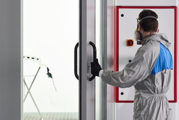 Mecánico que ingresa a la cabina de pintura en el servicio de reparación de automóviles para pintar el parachoques de un automóvil con rociador