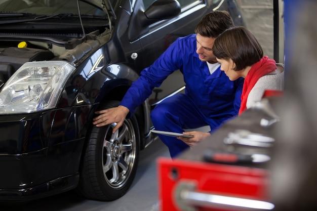 Mecánico que muestra al cliente el problema con el coche