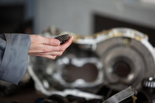 Mecánico que sostiene el engranaje cónico
