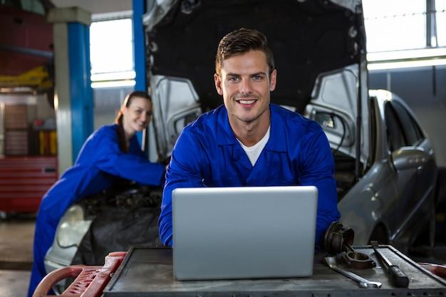 Mecánico que trabaja feliz en la computadora portátil