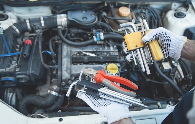 Mecánico que trabaja en reparación de automóviles. manos de herramientas
