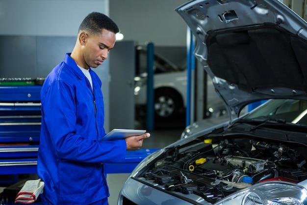 Mecánico que usa la tabla digital, mientras que el examen de los coches