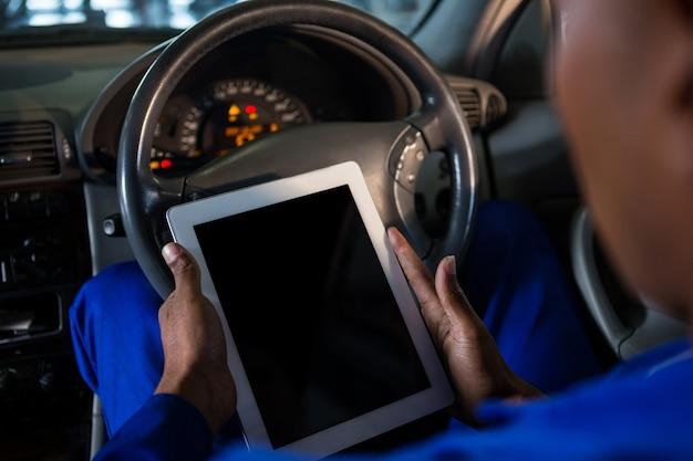 Mecánico que usa la tableta digital en el coche