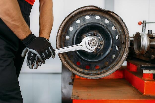 Mecánico repara un disco arrugado, servicio de reparación de neumáticos. hombre de reparación de neumáticos de coche en garaje, inspección de automóviles profesional en taller