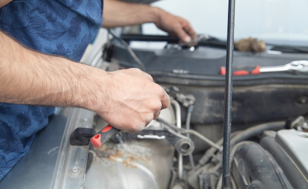 El mecánico repara el motor del coche. mantenimiento del auto