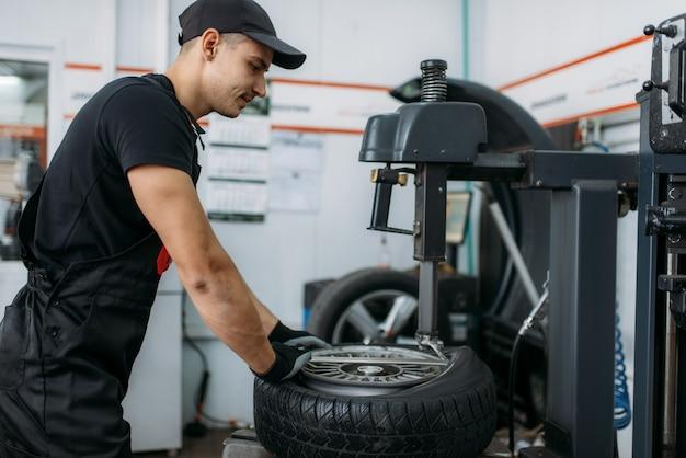 Mecánico de reparación de rueda rota en máquina de montaje de neumáticos, servicio de reparación. el hombre repara el neumático de automóvil en el garaje, inspección de automóviles en el taller