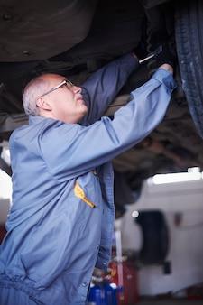 Mecánico reparando un coche en el taller.