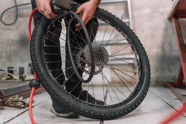 Mecánico reparando un neumático de bicicleta desinflado en un pequeño taller.