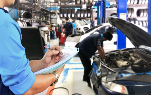 El mecánico está revisando la lista de reparación del motor en el garaje.