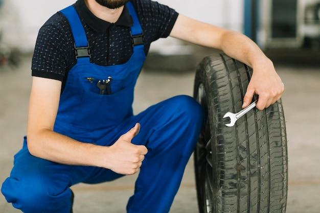 Mecánico con rueda en el taller