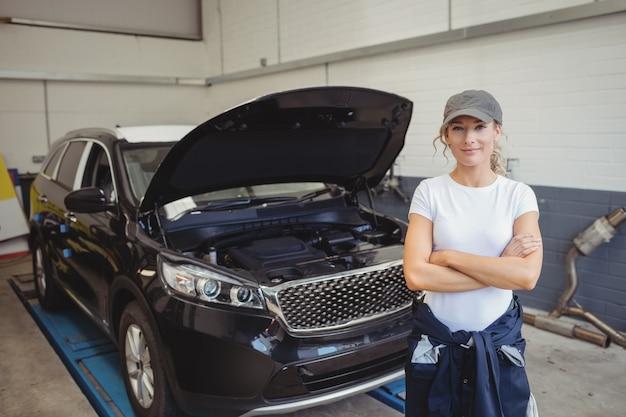 Mecánico de sexo femenino de pie con los brazos cruzados delante del coche
