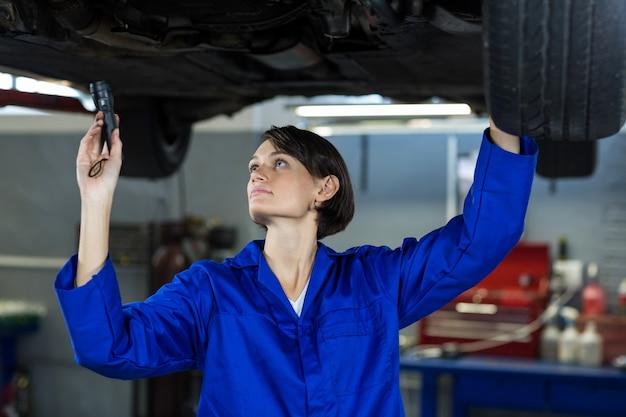 Mecánico de sexo femenino que examina a un coche con la linterna
