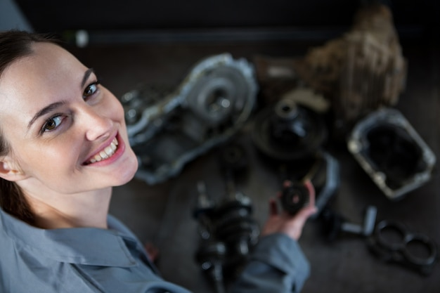 Mecánico de sexo femenino que sostiene las piezas de repuesto de coche