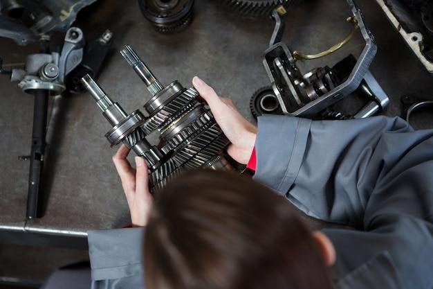 Mecánico de sexo femenino que sostiene las piezas de repuesto