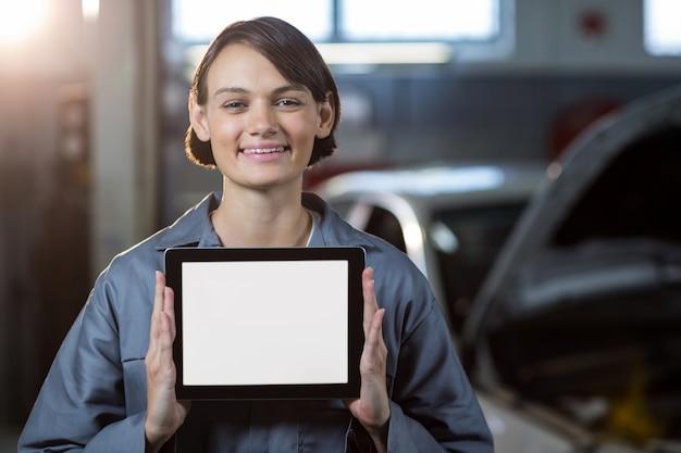 Mecánico de sexo femenino que sostiene la tableta digital