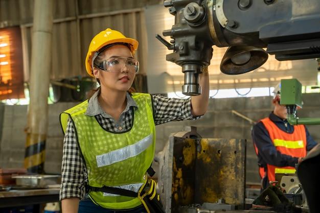 Mecánico de sexo femenino que trabaja y que comprueba la máquina en fábrica.