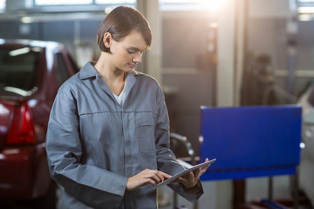 Mecánico de sexo femenino que usa la tableta digital