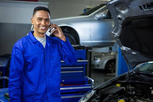 Mecánico sonriente hablando por un teléfono móvil