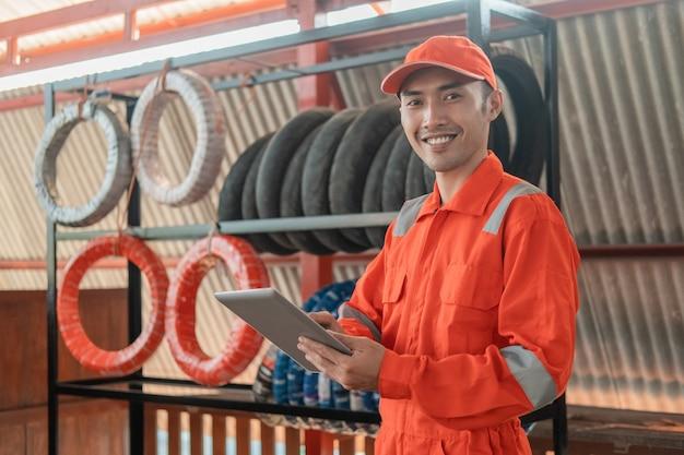 Mecánico sonriente en wearpack usando una tableta digital mientras está en el taller con una rejilla para neumáticos detrás