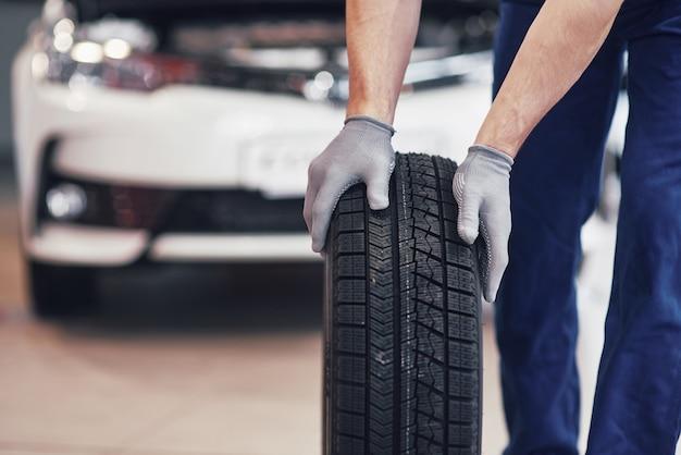 Mecánico sosteniendo un neumático en el garaje de reparación. reemplazo de neumáticos de invierno y verano