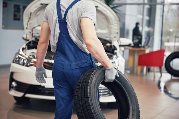 Mecánico sosteniendo un neumático en el garaje de reparación.