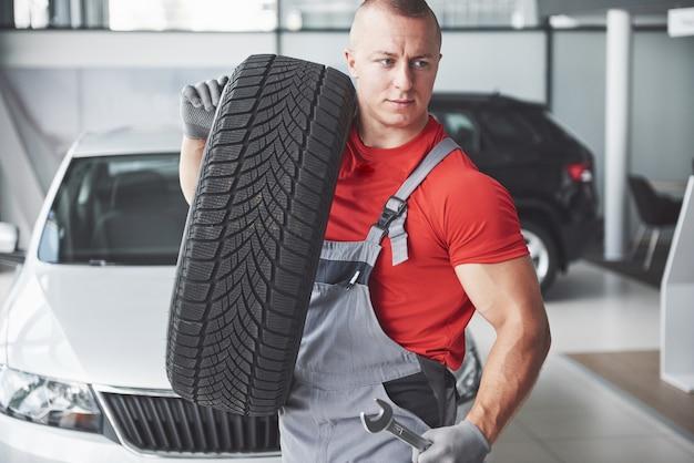 Mecánico sosteniendo un neumático en el taller de reparación. sustitución de neumáticos de invierno y verano.