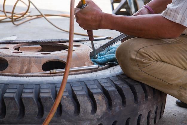 Mecánico en su taller que reemplaza neumáticos. reparación de neumáticos. la reparación del neumático por parte del trabajador.