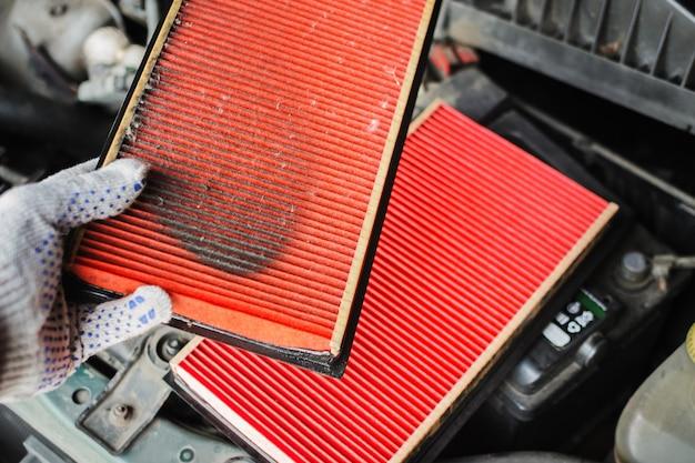 Mecánico sustituye el filtro de aire en el coche.