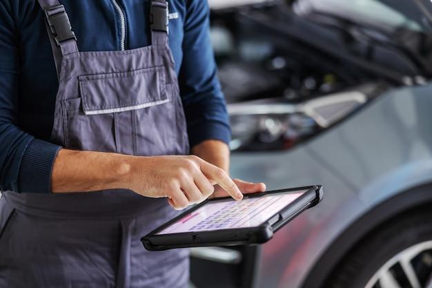 Mecánico con tableta para diagnosticar un problema de automóvil. garaje del interior del salón de coches.