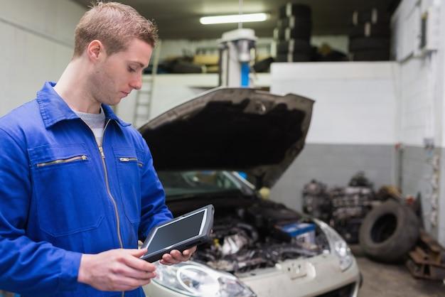 Mecánico con tableta digital en el garaje
