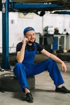 Mecánico con teléfono en la rueda en el taller