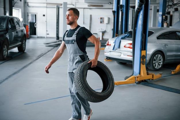 Mecánico tiene un neumático en el taller de reparación