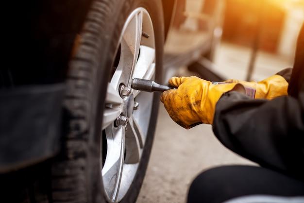 Un mecánico trabajador experimentado con guantes naranjas está usando una llave eléctrica para apretar los tornillos en una rueda de automóvil.
