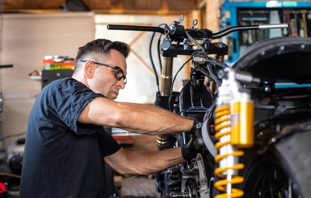 Mecánico trabajando en la reparación de una motocicleta en el taller.