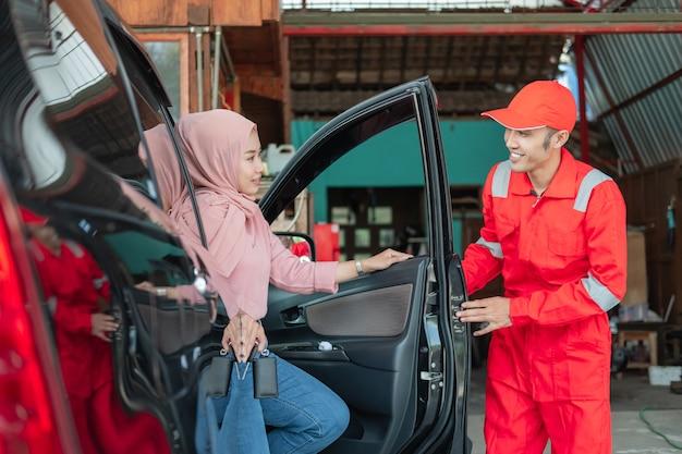El mecánico de uniforme rojo cierra la puerta del cliente después de que el automóvil sea reparado en el garaje.