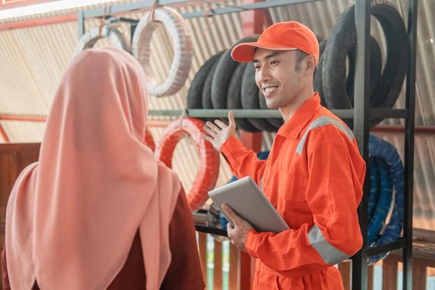 Mecánico en uniforme wearpack sosteniendo tableta digital mientras atiende a clientas con velo seleccionando neumáticos en el taller