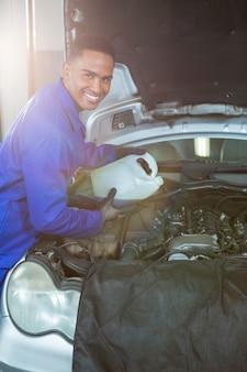 Mecánico verter lubricante de aceite en el motor de un coche