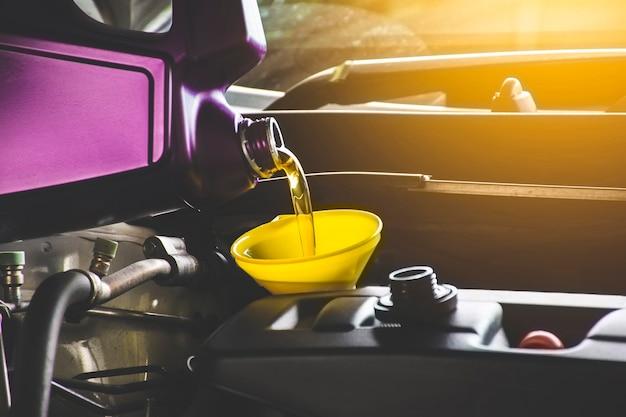 Mecánico vertiendo aceite de motor al motor del automóvil