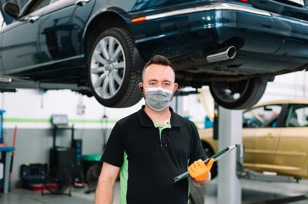 Mecánico vistiendo mascarilla quirúrgica sosteniendo un portapapeles trabajando en el servicio de reparación de garaje