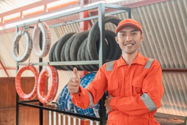 Mecánico en wearpack rojo con los pulgares hacia arriba mientras está en el taller con una rejilla para neumáticos detrás