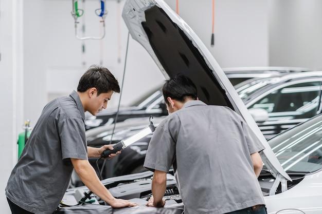 Los mecánicos asiáticos abren el capó del auto y revisan el motor en el centro de servicio de mantenimiento