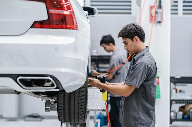 Mecánicos asiáticos que controlan las ruedas del automóvil en el centro de servicio de mantenimiento en la sala de exposición