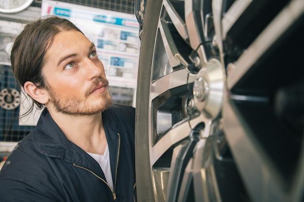 Mecánicos guapos en uniforme están trabajando en servicio de automóviles con llantas de aleación.