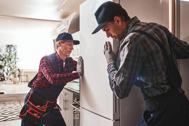 Mecánicos de hombres jóvenes fáciles de resolver controlando el refrigerador