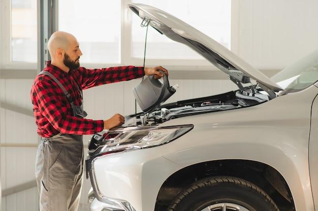 Mecánicos masculinos y femeninos trabajando en coche