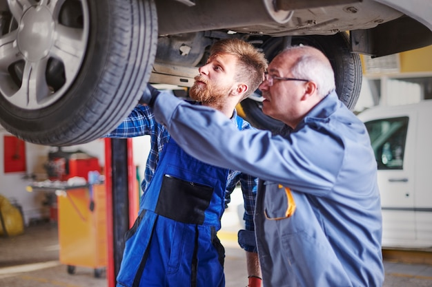 Mecánicos reparando un coche en el taller.